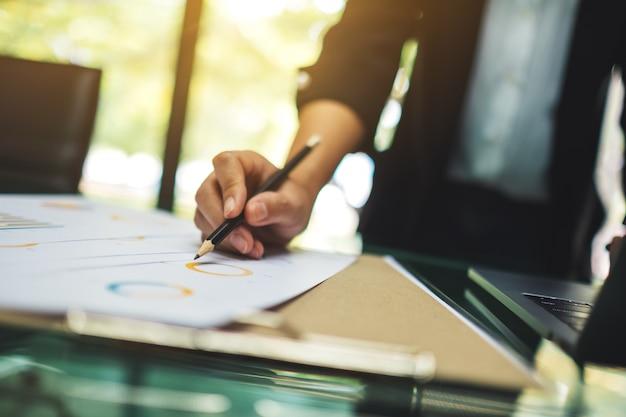 Uma empresária escrevendo e trabalhando em dados financeiros da empresa e computador laptop em cima da mesa no escritório