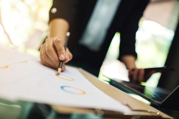 Uma empresária escrevendo e trabalhando em dados financeiros da empresa e telefone móvel em cima da mesa no escritório