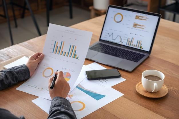 Uma empresária escrevendo e trabalhando em documentos e dados de negócios com o laptop na mesa do escritório
