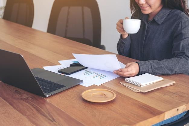 Uma empresária segurando e olhando para dados e documentos de negócios com o laptop na mesa enquanto bebe café no escritório