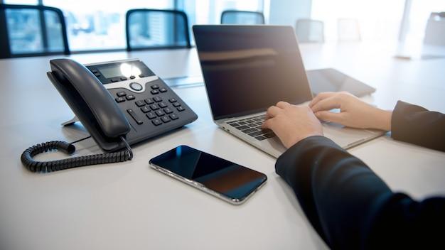 Uma empresária trabalhando tem um laptop para o trabalho, um smartphone e um telefone