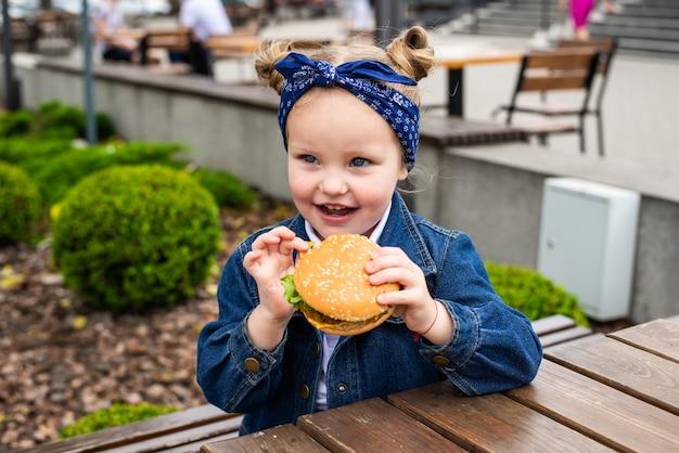 Uma encantadora girinha sorridente está segurando um hambúrguer ao ar livre em um dia ensolarado.