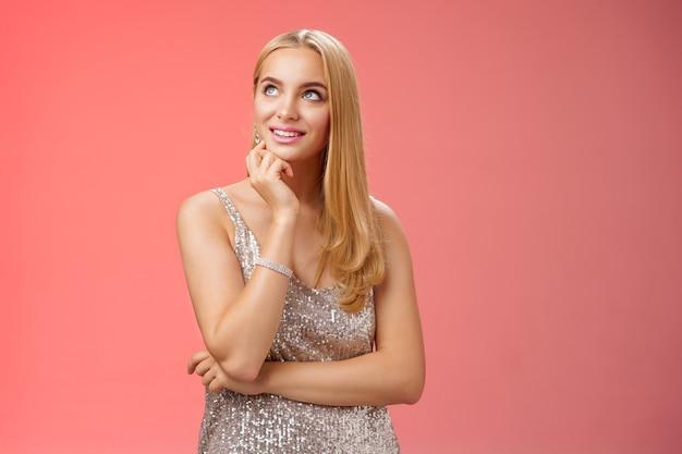 Uma encantadora jovem loira elegante sonhadora em um vestido de noite prateado brilhante olha pensativa aproveitando a pós-festa da semana da moda em pé casualmente relaxada fundo vermelho pensando em planejamento