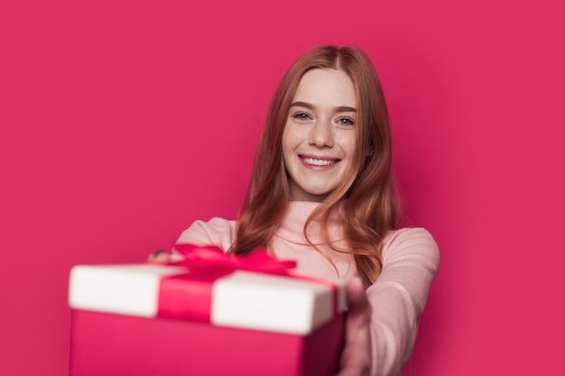 Uma encantadora mulher ruiva com sardas dando um presente para a câmera sorrindo na parede rosa do estúdio