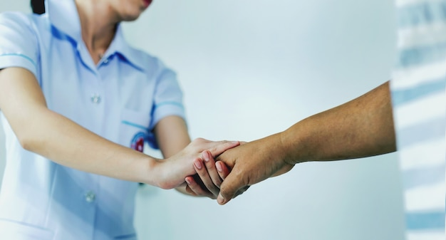 Uma enfermeira apertando as mãos para encorajar o paciente