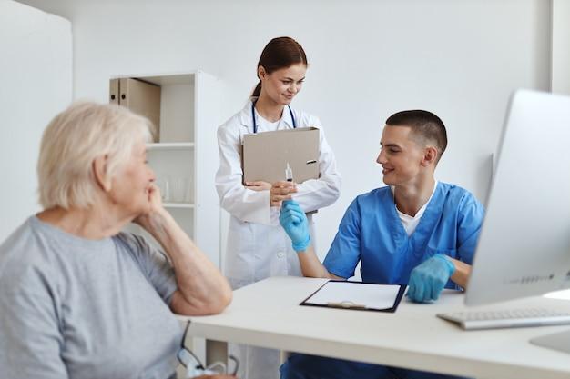 Uma enfermeira e um médico examinam um paciente em um hospital