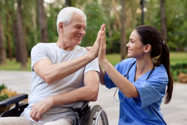 Uma enfermeira e um velho em uma cadeira de rodas alto cinco.