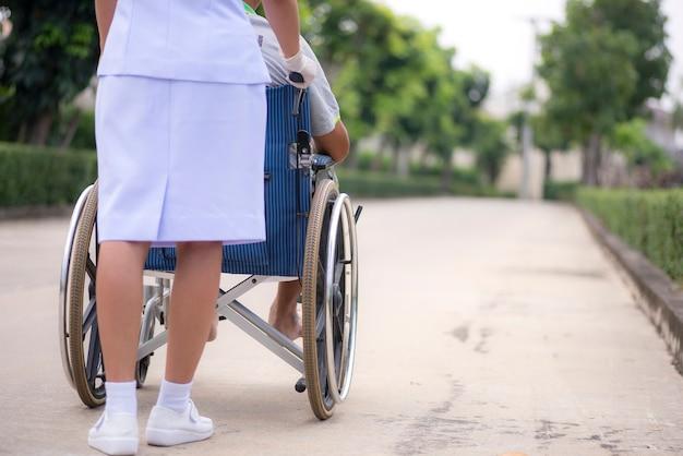 Uma enfermeira está empurrando uma cadeira de rodas para um paciente no parque