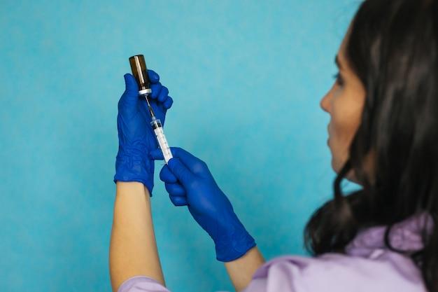 Uma enfermeira ou médico com luvas médicas azuis disca o medicamento em uma seringa.