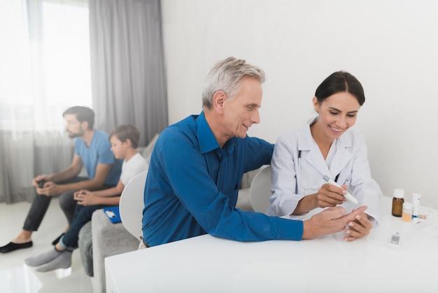 Uma enfermeira pega uma amostra de sangue com o escarificador de um velho