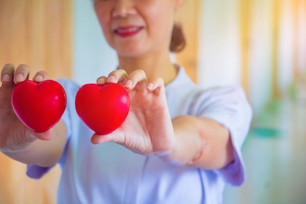 Uma enfermeira que prende o brinquedo vermelho do coração. a foto mostra o princípio de cuidar e de boa saúde.