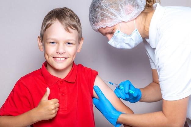 Uma enfermeira usando uma máscara e luvas azuis injeta a vacina por meio de uma seringa em um menino
