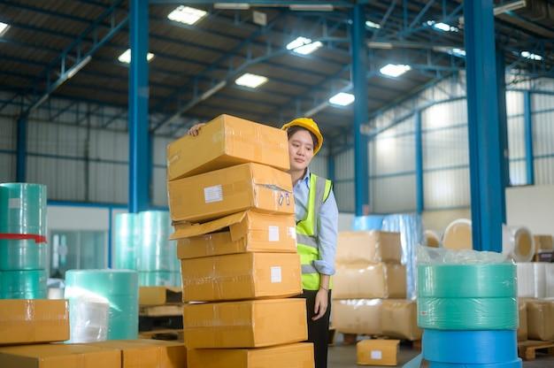 Uma engenheira asiática está trabalhando em um armazém moderno
