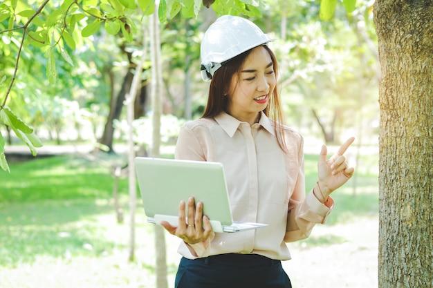 Uma engenheira usando um chapéu de segurança branco. ela trabalha com o meio ambiente. segurando um notebook, verificando informações