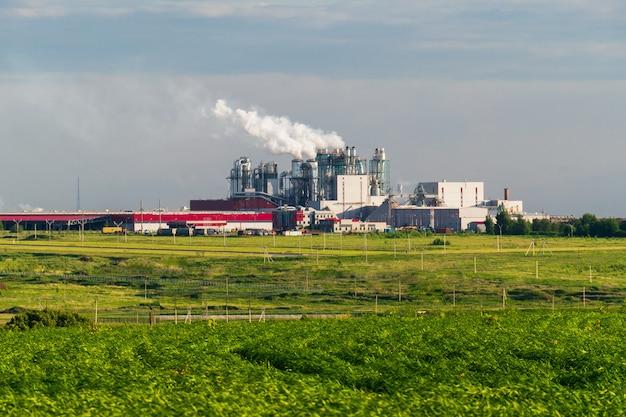 Uma enorme fábrica de concreto com tubos entre os campos