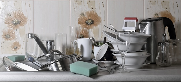 Uma enorme pilha de pratos não lavados na pia da cozinha e na bancada