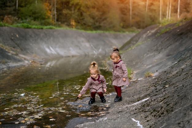 Uma enorme poça cinza com costões rochosos no meio de uma floresta de outono onde as meninas brincam