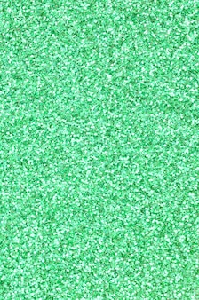 Uma enorme quantidade de lantejoulas decorativas verdes. imagem com luzes brilhantes bokeh de pequenos elementos