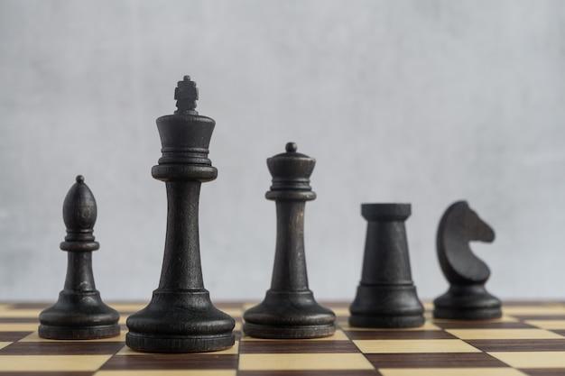 Uma equipe de figuras pretas de xadrez no tabuleiro