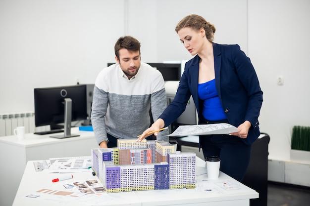 Uma equipe de jovens arquitetos trabalhando na finalização de seus modelos de construção