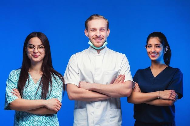 Uma equipe de jovens médicos. pessoas multinacionais - médico, enfermeiro e cirurgião em fundo azul. um grupo de estudantes de medicina de diferentes nacionalidades está olhando na cela.
