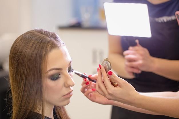 Uma equipe de maquiadores trabalha com o rosto de uma linda jovem