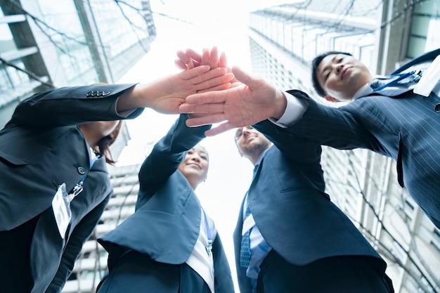 Uma equipe de negócios de mãos dadas nas ruas do distrito comercial