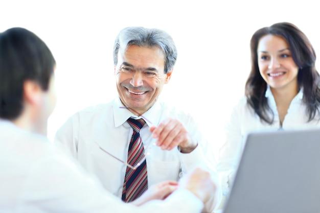 Uma equipe de negócios de três pessoas sentadas no escritório e planejando o trabalho
