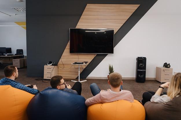 Uma equipe de ti jogue videogame no console enquanto relaxa depois do trabalho