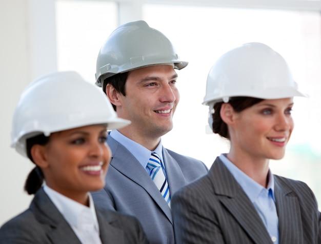 Uma equipe diversificada de arquitetos em pé durante uma conferência
