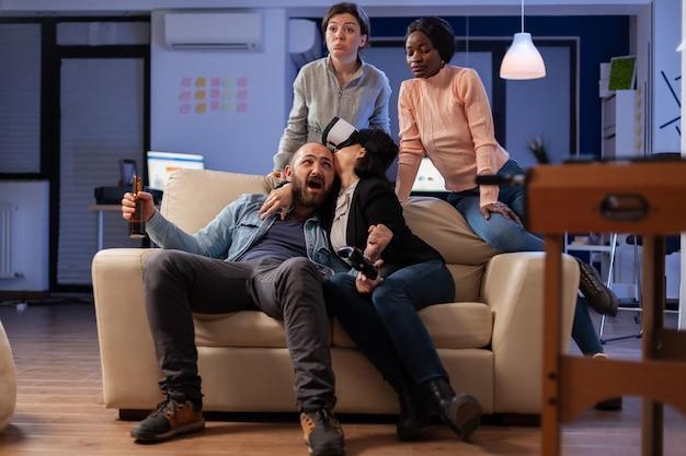 Uma equipe multiétnica de companheiros joga com óculos vr após o trabalho