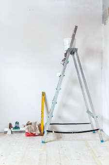 Uma escada com ferramentas de pintura em um cômodo de uma casa ou apartamento. preparação para massa na parede ou pintura. conceito de reparo ou renovação em casa.