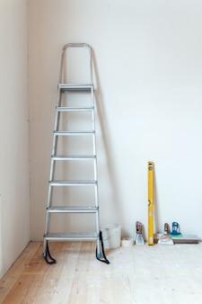 Uma escada com ferramentas de pintura em um cômodo de uma casa ou apartamento