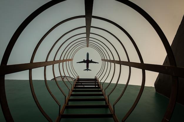 Uma escada de aço circular com um avião no céu ao pôr do sol
