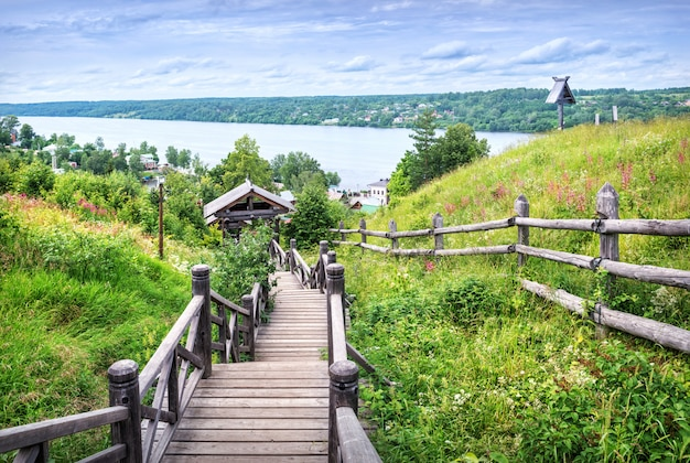 Uma escada de madeira do monte levitan com vista para o rio volga, na cidade de plyos, entre a vegetação do verão e as flores dos prados