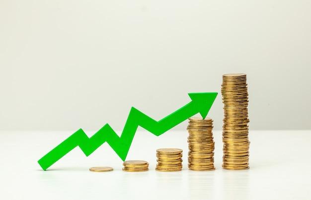 Uma escada de moedas de ouro e uma seta verde para cima. conceito de crescimento do lucro.