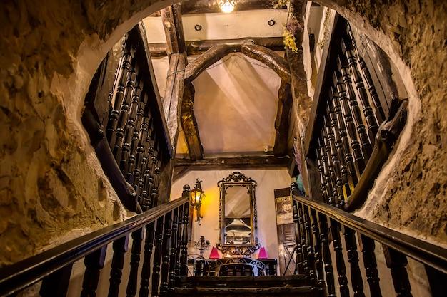 Uma escada que leva a um espelho na casa de uma bruxa.