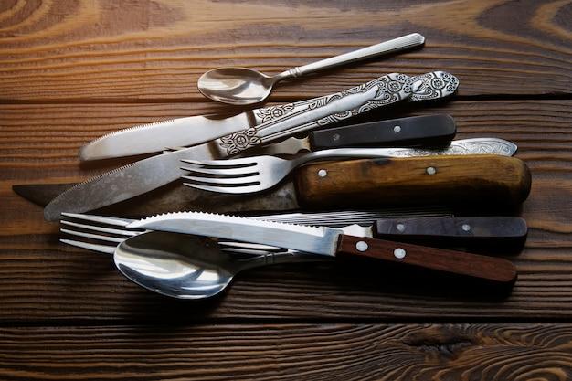 Uma escala da cutelaria diferente do vintage com as facas, as forquilhas e as colheres vistas de cima sobre de madeira textured.