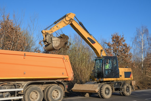 Uma escavadeira balde limpa a beira da estrada. obras rodoviárias. colocando uma nova estrada. carregando pedras e argila da escavadeira