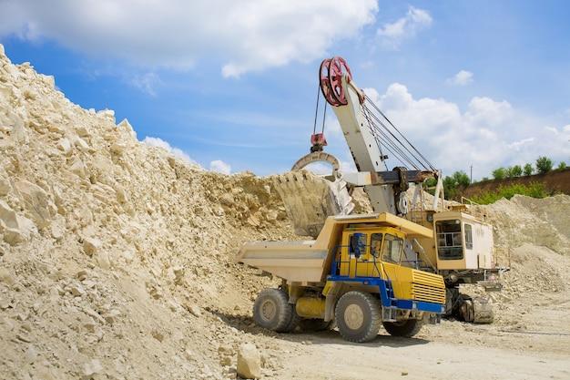 Uma escavadeira carrega um enorme caminhão com pedras
