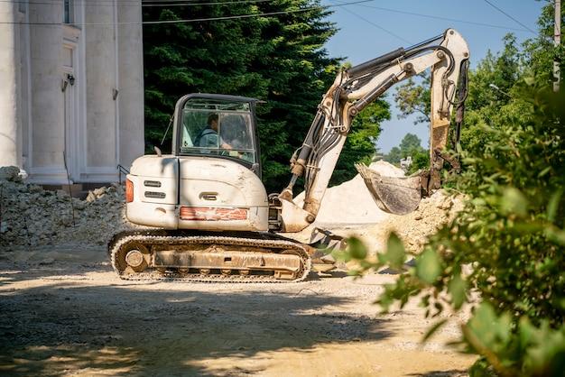 Uma escavadeira com bulldozer trabalhando na rua, construindo uma estrada e pavimento Foto Premium