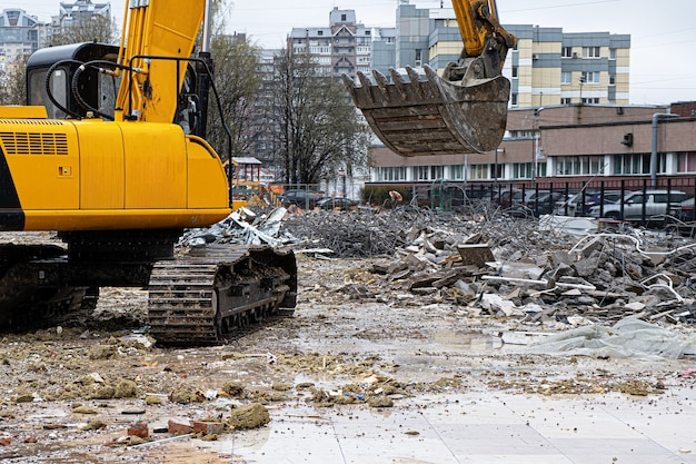 Uma escavadeira entre uma pilha de lixo após a desmontagem de um prédio construído ilegalmente.