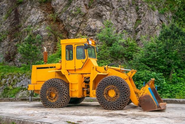 Uma escavadora enorme está esperando o tempo da neve no canteiro de obras.