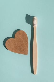 Uma escova de dentes de madeira ecológica de bambu e um coração de madeira em um fundo azul claro