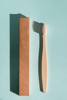 Uma escova de dentes de madeira ecologicamente correta e uma caixa de escova de dentes em um fundo azul claro luz forte
