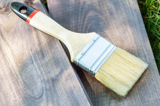 Uma escova de pintura larga encontra-se em uma placa de madeira na grama verde no close-up da rua. pincel em madeira