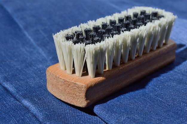 Uma escova de roupas repousa sobre jeans dobrados.