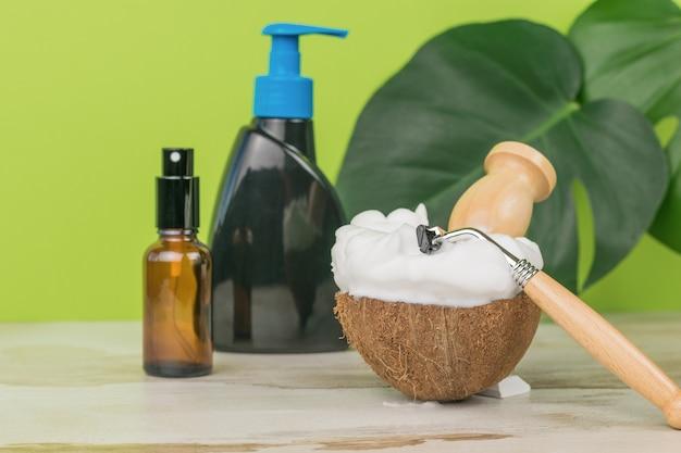 Uma escova e uma lâmina de barbear em uma tigela com muita espuma de barbear e acessórios de lavagem.