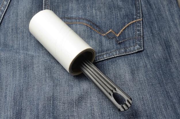 Uma escova para roupas pegajosa enrolada em rolos repousa sobre jeans escuros.
