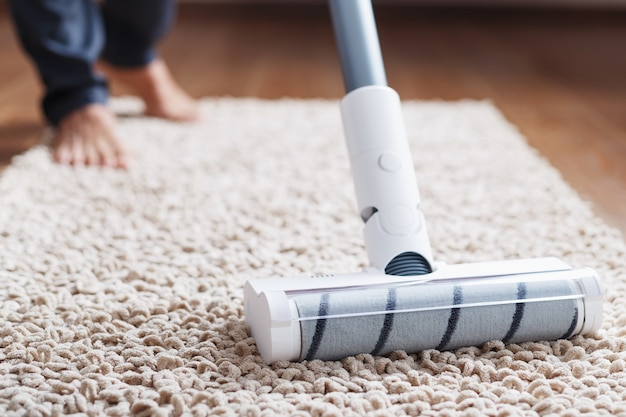 Uma escova turbo branca de um aspirador de pó sem fio no carpete. conceito de limpeza interna